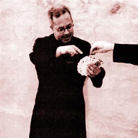 Padre Cimò mentre esegue una magia con le carte da gioco